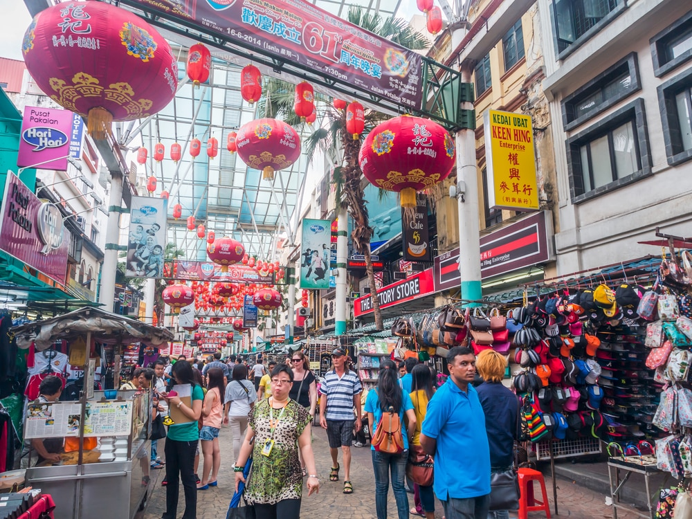 People walk through a busy China town at Petaling Street, Malays